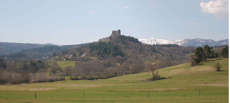 Château de Murat et massif du Sancy enneigé au fond