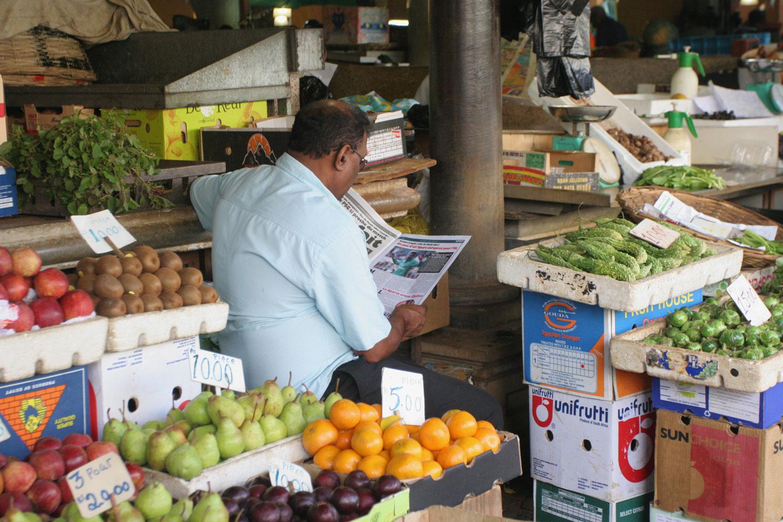 Pause lecture d'un marchant de Port-Louis (Île Maurice)