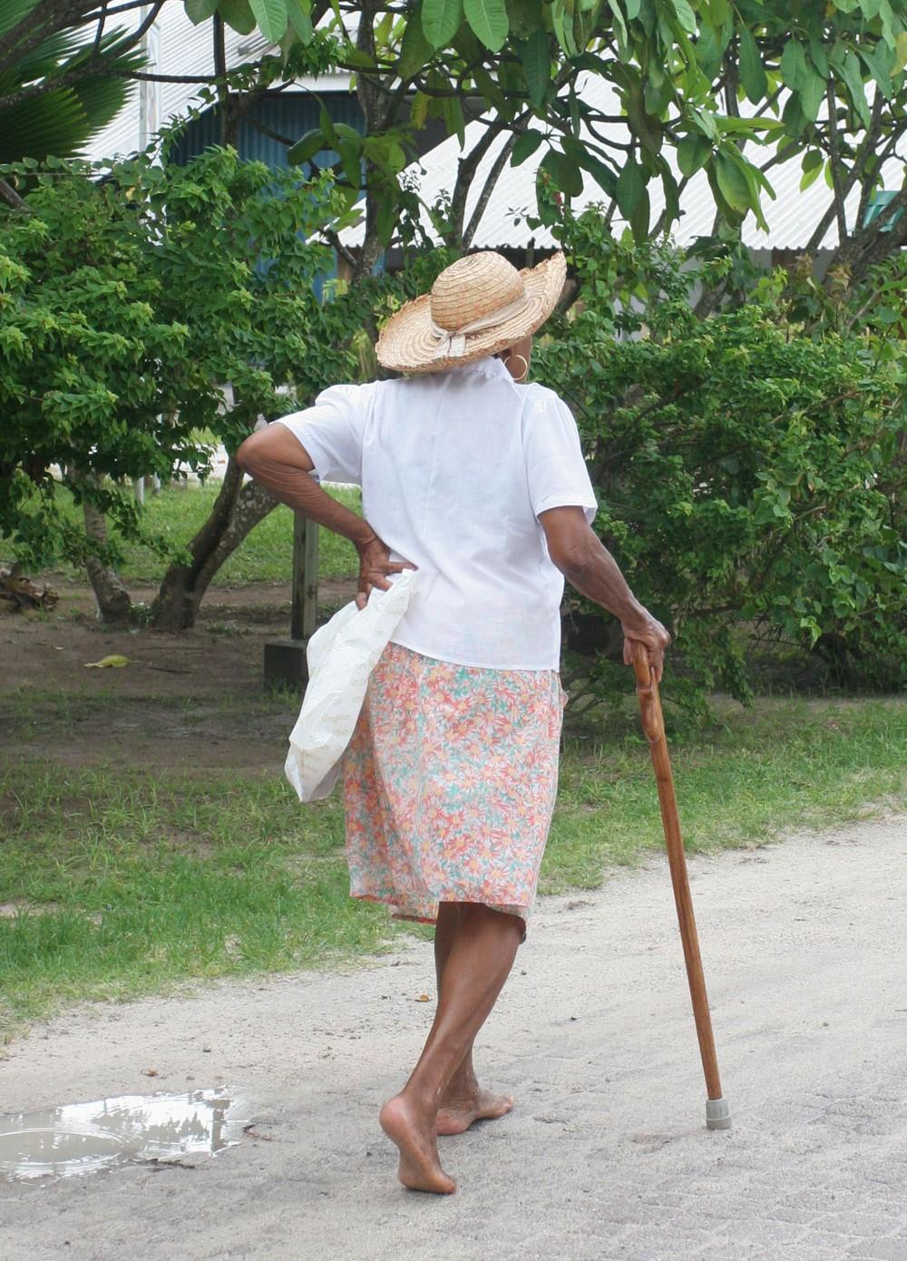 Dame âgée marchant à La Passe, île de La Digue (Seychelles)